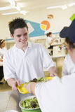 A student collecting lunch in school cafeteria Stock Image