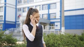 Schoolgirl teenager gets home from school and talking on the phone with a friend. stock video footage
