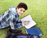 Student collegu czyta nad trawą. Obrazy Royalty Free