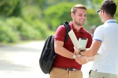Student collegu szczęśliwy spotykać jego przyjaciela i wtedy trząść ręki fotografia royalty free
