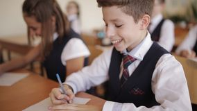 Student collegu w mundurku szkolnym piszą certyfikat pracie test ucznie zbiory wideo