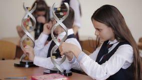 Student collegu w mundurku szkolnym studiują układ DNA i patrzeją przez mikroskopu podczas gdy siedzący w a zdjęcie wideo