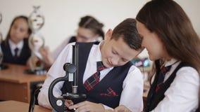 Student collegu w mundurku szkolnym studiują układ DNA i patrzeją przez mikroskopu podczas gdy siedzący w a zbiory