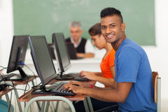 Student computer class. Handsome indian college student typing in computer class Stock Photography