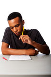 Student concentrating for test exam. Handsome student thinking concentrating focussing for test examination sitting at desk, on white Royalty Free Stock Photography