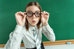 Student in confusion near blackboard, correcting glasses. Photo of young students in classroom, education concept Stock Photos