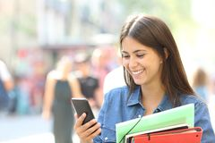 Student consulting online information in a phone. Happy student consulting online information in a smart phone in the street Stock Images