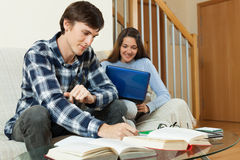 Student couple with books and laptop preparing for exams Royalty Free Stock Image