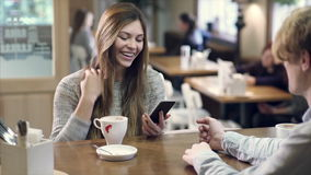 Student couple chatting together in a cafe. Student couple chatting together in the cafe having coffee. Man takes photo of his girlfriend by smartphone. ProRes stock video footage
