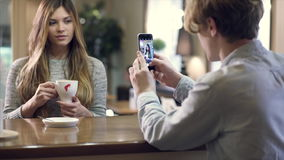 Student couple chatting together in a cafe. Student couple chatting together in the cafe having coffee. Man takes photo of his girlfriend by smartphone. ProRes stock video