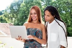Student couple with computer reading internet news royalty free stock image
