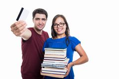 Student couple showing credit card and holding books. Student couple showing credit card and holding pile of books isolated on white background with copypsace royalty free stock image