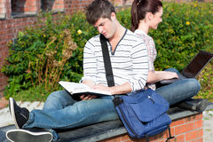 Student couple using a laptop and reading a book. Couple of students using a laptop and reading a book sitting in the campus of their university Royalty Free Stock Image