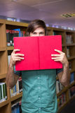 Student covering face with book in library Royalty Free Stock Photography