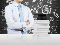 Student with the crossed hands is standing in front of the books and a graduation hat. Stock Photo