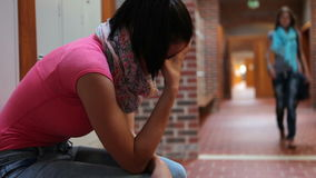Student crying in hallway being comforted by friend