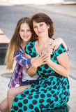 Student daughter hugging mother on bench on street Stock Images