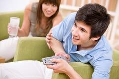 Student - de gelukkige afstandsbediening van de tienerholding royalty-vrije stock afbeelding
