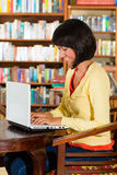 Vrouw in bibliotheek met laptop Stock Foto