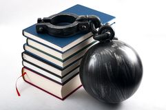 Student debt concept with a stack of books next to a ball and chain symbolizing the burden tuition costs represent isolated on. White royalty free stock images