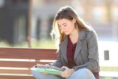 Student, der Anmerkungen auf einer Bank lesend lernt lizenzfreie stockfotos