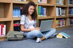 Student, der auf Boden in der Bibliothek unter Verwendung des Laptops sitzt Lizenzfreie Stockfotos