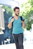 Student, der auf dem Campus mit Handy geht Lizenzfreies Stockbild