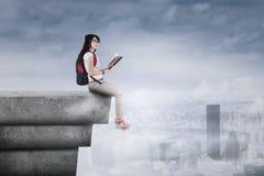 Student, der auf der Dachspitze sitzt Stockfotografie