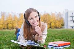 Student, der auf Kopfhörer hört und geöffnetes Buch hält Stockbild