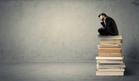 Student, der auf Stapel Büchern sitzt Lizenzfreie Stockfotografie