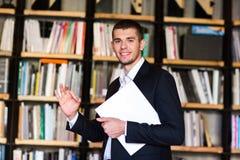 Student in der Bibliothek Hübscher junger Bücher haltener und bei der Stellung lächelnder Mann in der Bibliothek lizenzfreies stockbild