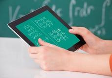 Student, der das mathematische Problem auf digitaler Tablette im Klassenzimmer löst lizenzfreies stockbild