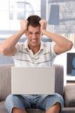 Student, der den Laptopbildschirm entsetzt betrachtet Lizenzfreies Stockfoto