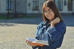 Student, der ein Buch, ein Buch auf dem Campus liest lizenzfreies stockfoto