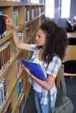 Student, der ein Buch vom Regal in der Bibliothek auswählt Stockbilder