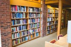 Student, der ein Buch vom Regal in der Bibliothek liest Stockfotos