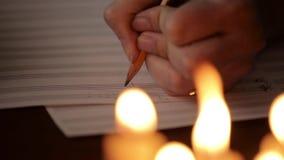 Student, der eine Musik schreibt: Musiker, der mit einem Bleistift in einem Musikbuch verfasst Musikalischer Personal stock video footage