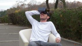 Student, der in einem Lehnsessel Schutzbrillen einer in den tragenden virtuellen Realität des Parks ansehen furchtsamen 3d Inhalt stock video