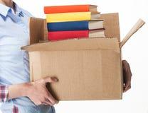 Student, der einen großen Kasten mit Stapel Büchern hält Stockfoto