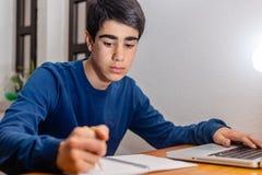 Student, der Hausarbeit an seinem Schreibtisch mit Laptop tut stockfotografie