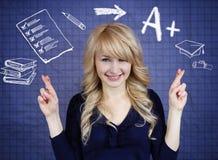 Student, der ihre Finger, hoffend für die besten, guten Grade in der Schule kreuzt Stockbild