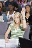 Student, der ihre Hand zur Antwort anhebt Stockbild