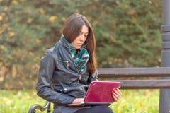 Student, der Laptop auf Parkbank verwendet Stockbild
