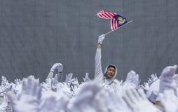 Student, der Malaysia-Flagge alias Jalur Gemilang wellenartig bewegt Stockfotos