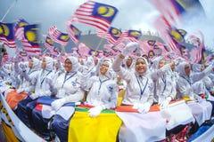 Student, der Malaysia-Flagge alias Jalur Gemilang wellenartig bewegt Lizenzfreie Stockfotografie