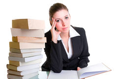 Student, der mit Stapel der Bücher auf dem Schreibtisch lernt Stockbilder
