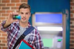 Student, der seine Karte zur Kamera am ATM zeigt Lizenzfreie Stockfotos
