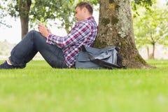 Student, der seine Tablette verwendet, um draußen zu studieren Stockbilder