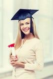 Student in der Staffelungskappe mit Zertifikat Stockfotos
