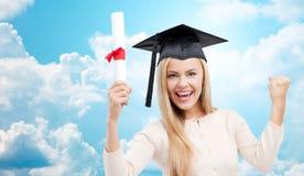 Student in der Trencherkappe mit Diplom über blauem Himmel Stockfoto